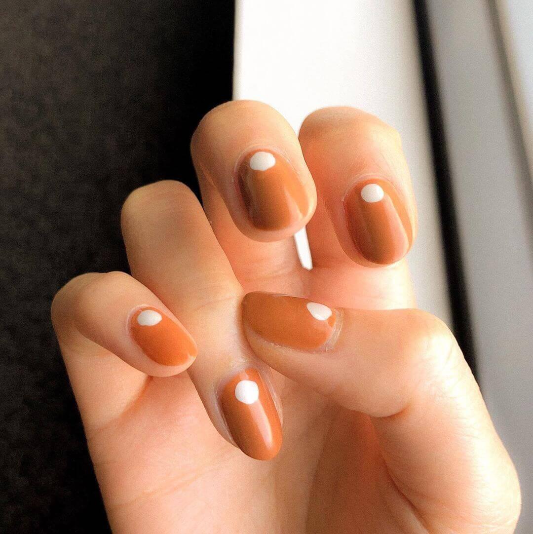 uñas naranja con puntos blancos