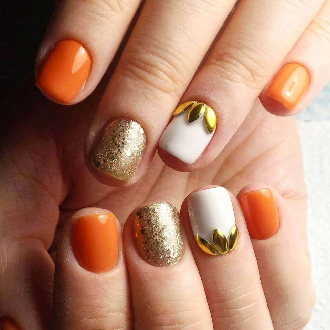 uñas naranja decoradas con dorado