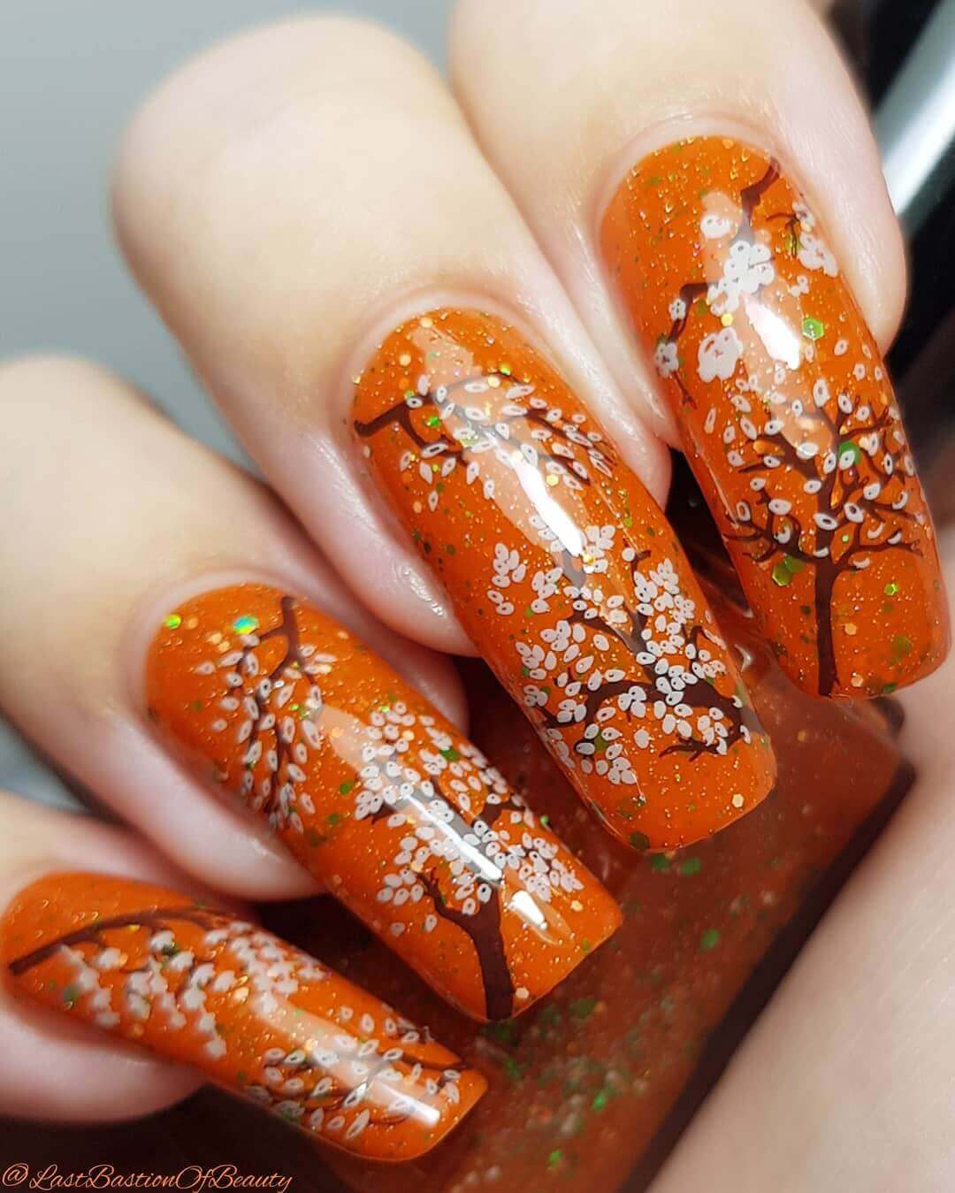uñas naranja decoradas con flores