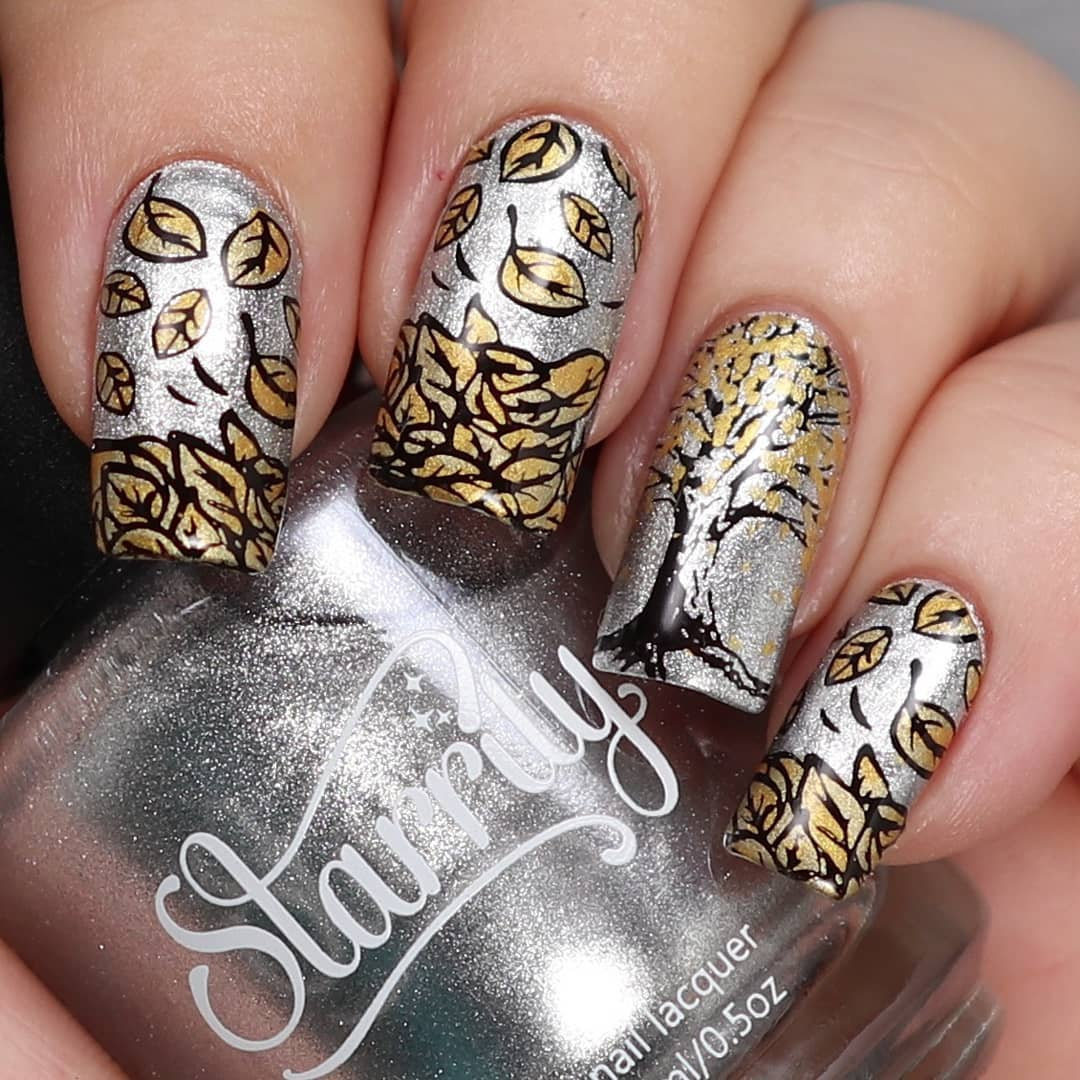 uñas plateadas con estampado dorado