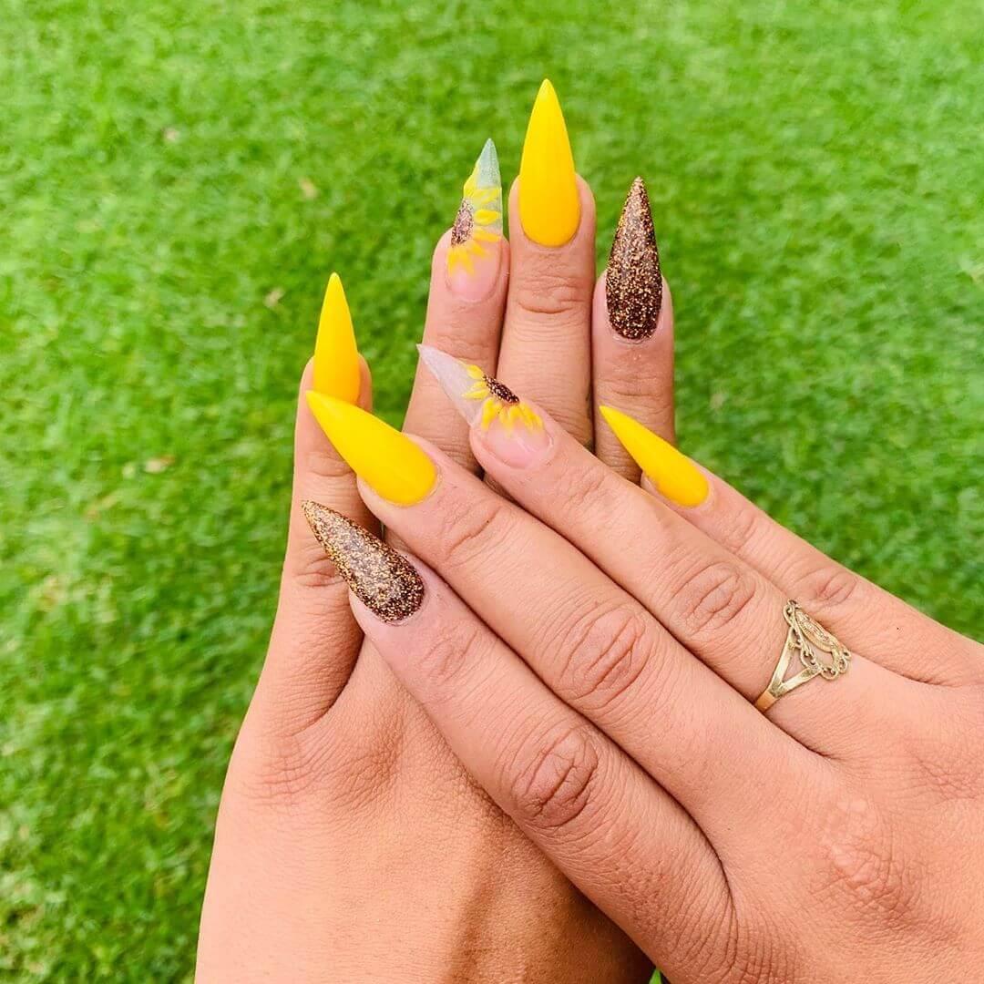 uñas stiletto amarills con dorado