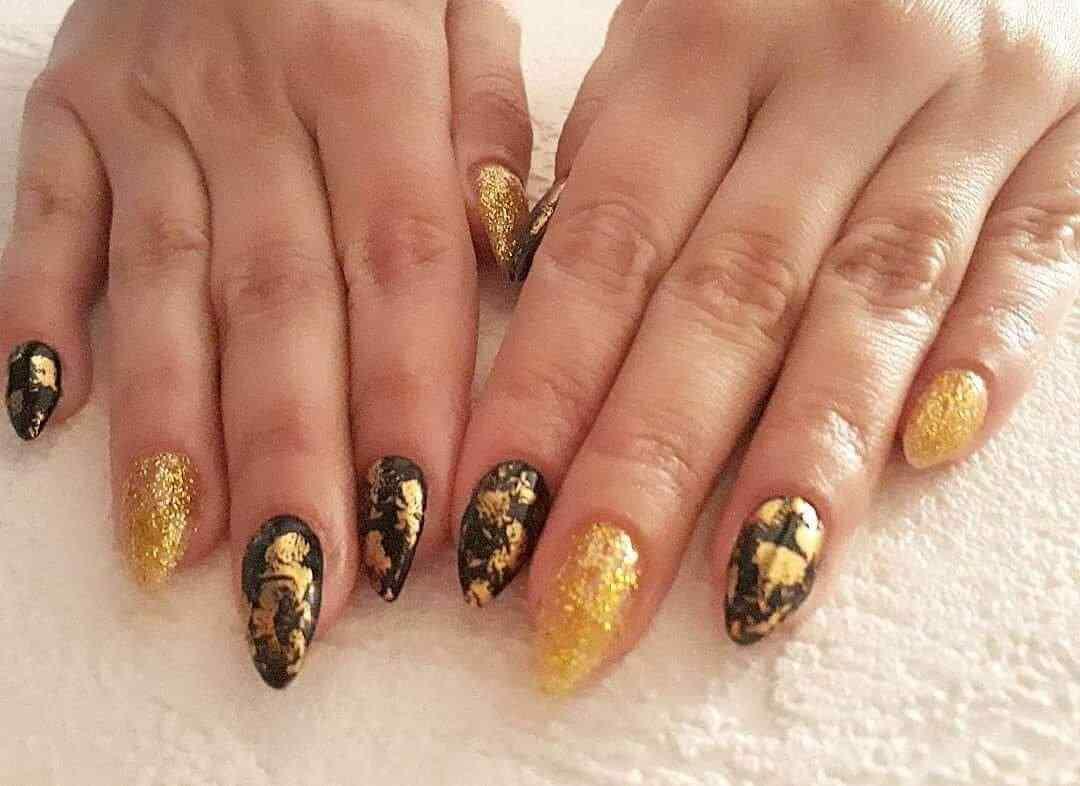 uñas negras con dorado y piedras