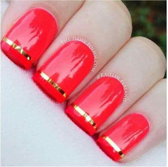 uñas rojas con cinta dorada