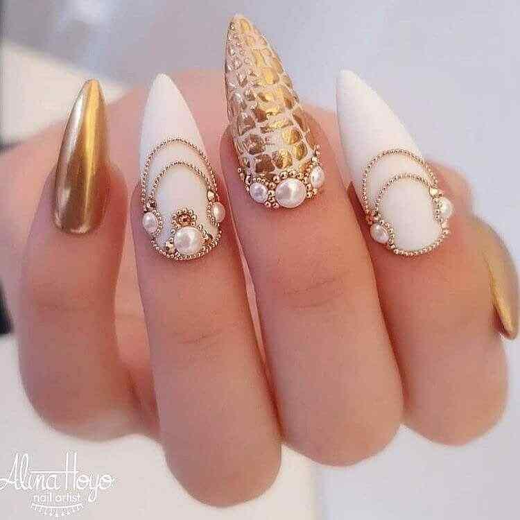 decoración elegante de uñas blancas dorado piedritas accesorios