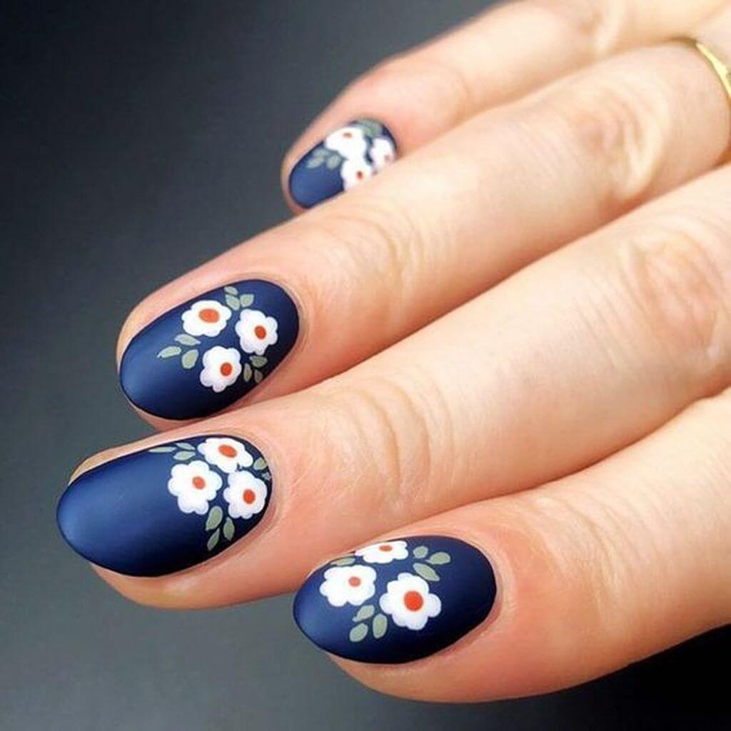 uñas con flores sobre base azul